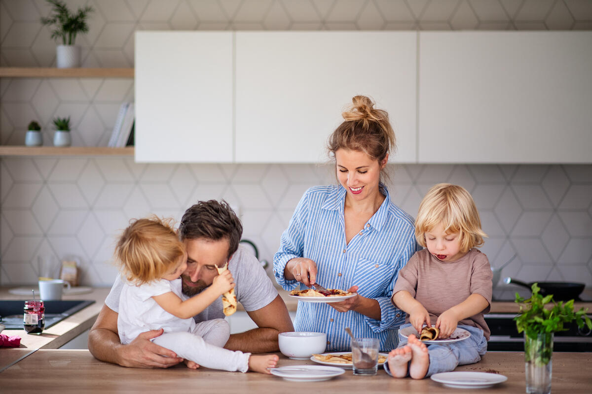 family cooking in kitchen-white-cabinets